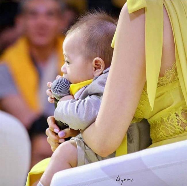 Cậu nhóc đáng yêutranh thủ gặm mic khi mẹ ôm trong lòng.