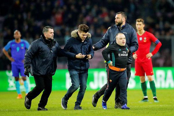 Các nhân viên bảo vệ chạy vào sân đưa nhóm fan nam ra ngoài để trận đấu tiếp tục.