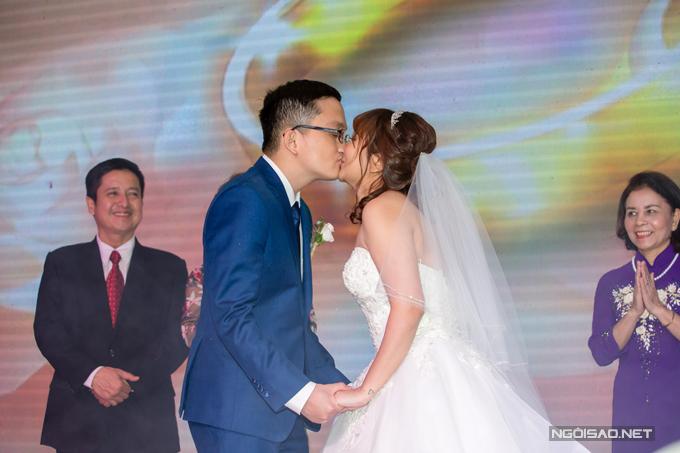 Cặp đôi trao nhau nụ hôn ngọt ngào trước sự chứng kiến của bố mẹ và bạn bè.