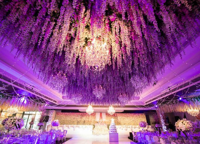 Toàn bộ không gian tiệc cưới hình chữ T được phủ kín bằng hoa, cả trên trần nhà. Tất cả các vật dụng trang trí tạo cho tổng thể sự lộng lẫy nhưng vẫn trang nhã,hài hòa.