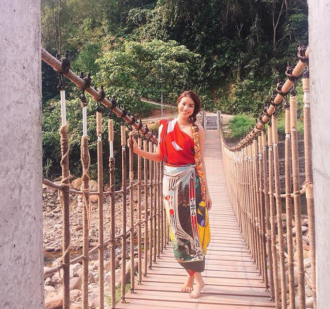 Phạm Hương dùng khăn hàng hiệu làm váy quấn, đi chân đất lên cây cầu treo bắc qua sông ở Huế.
