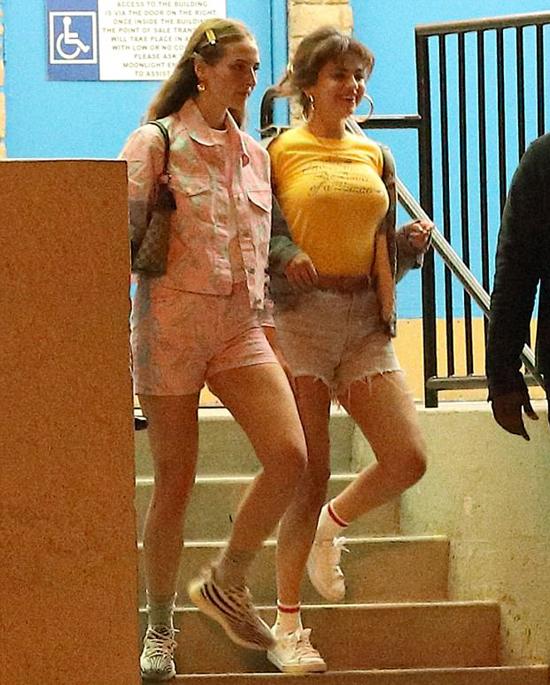 Selena Gomez tươi tắn cùng người bạn rời khu vui chơi giải trí Moon Light Rollerway ở Los Angeles tối 27/3.