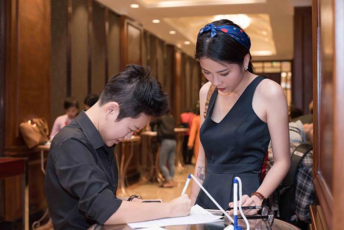 Cặp đôi mặc ton-sur-ton đen khi đến buổi casting. Bảo Thy giúp người yêu điền vào bảng đăng ký dự thi.