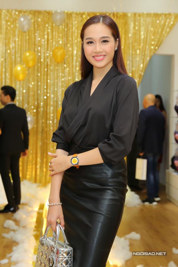 Lê Thu An phối áo lụa cùng chân váy bút chì trên chất liệu da đen, phụ kiện đi kèm là túi Dior màu ánh bạc bắt mắt.