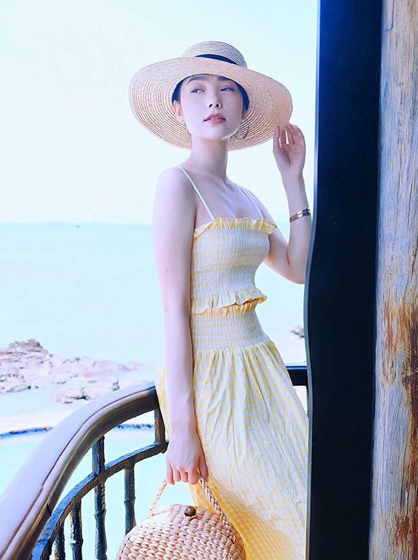 Cũng diện thiết kế hai dây tôn vẻ đẹp sexy nhưng ca sĩ Minh Hằng lại diện áo crop top trang trí bèo nhún tiệp màu với chân váy ngắn. Phụ kiện đi kèm là mũ rộng vành và túi đan dây lục bình đậm chất mùa hè.