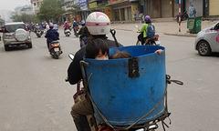 Cha chở con trong thùng đựng cá chạy băng băng trên đường