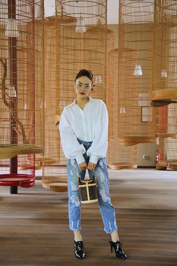 Sơ mi tay bồng hot trend của mùa mốt mới được Minh Hằng chọn lựa để kết hợp cùng quần jean rách. Cô tạo thêm điểm nhấn cho tổng thể bằng mẫu túi xách tay mới ra lò của thương hiệu Louis Vuitton.