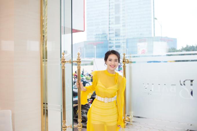 Cô nàng diện chiếc đầm vàng xuyên thấu nổi bật,nở nụ cười rạng rỡ.