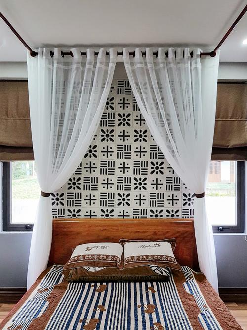 Phòng ngủ của vợ chồng anh Hùng được trang bị rèm voan trắng với mảng gạch trang trí hút mắt.