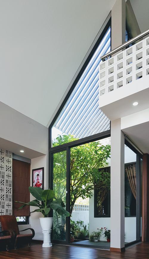 Bên cạnh gạch thông gió, nam kiến trúc sư sử dụng tường kính để tận dụng tối đa ánh sáng cho ngôi nhà. Từ phòng khách của gia đình anh Hùng, dễ dàng nhìn ngắm khung cảnh xanh mát ở sân sau.