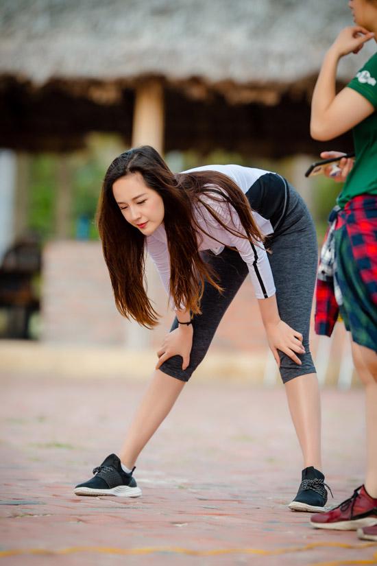 Người đẹp mặc đồ thể thao khỏe khoắn, khởi động kỹ cơ thể trước khi chạy.
