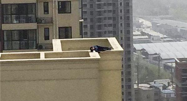 Người đàn ông với ý định tự sát nằm chênh vênh ngay mép tầng thượng.
