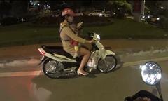 Mẹ địu con trước ngực vừa chạy xe máy vừa dùng điện thoại