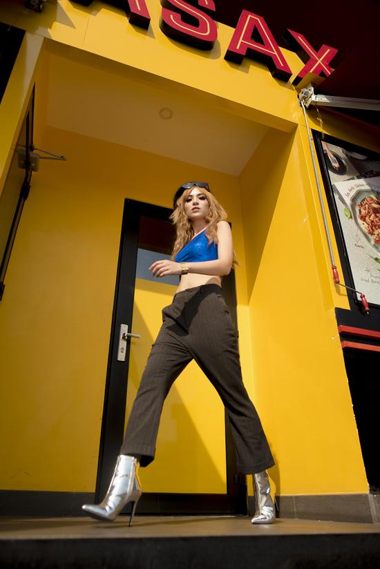 Nữ ca sĩ khoe vóc dáng cân đối, vòng eo thon với áo crop-top ánh nhũ xanh, quần ống vẩy và bốtcổ ngắn ánh bạc.