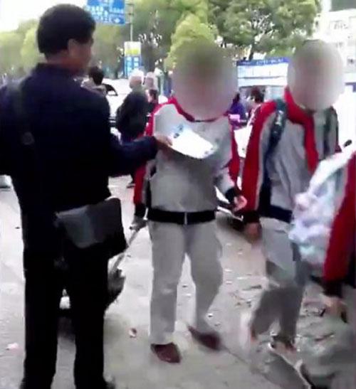 Tay của người đàn ông vừa cầm tờ rơi vừa sợ ngực nữ sinh.