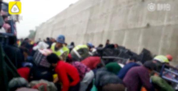 Người dân chen chúc nhặt táo quanh chiếc xe tải bị lật.