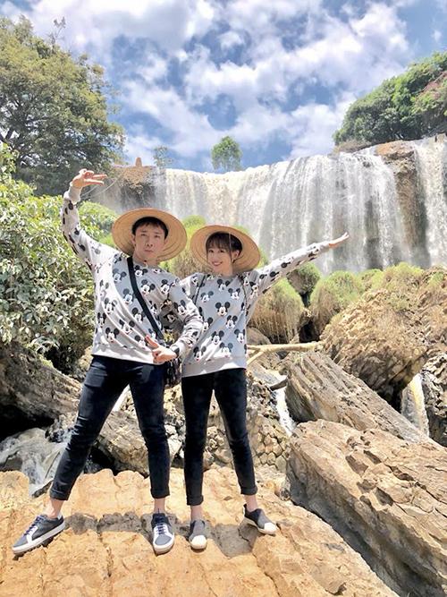Vợ chồng Hari - Trấn Thành mặc đồ đôi, tạo dáng cute trước một ngọn thác ở Đà Lạt.