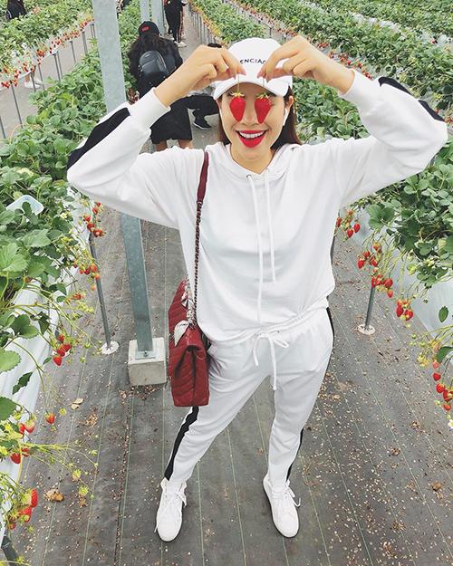 Phạm Hương hớn hở tạo dáng với hai quả dâu khi đi thăm khu vườn.