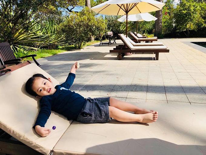 Kubi nằm thảnh thơi, sưởi nắng trên băng ghế dài trong khu resort.