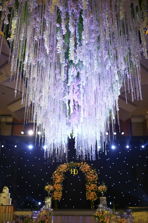Cùng với hoa tươi, hệ thống ánh sáng cũng là điểm đặc biệt trong hôn lễ này. Một chiếc đèn chùm bằng pha lê được treo ở khu vực sân khấu, xem kẽ là những dải hoa tử đằng mềm mại.