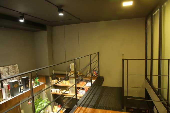 Cầu thang dẫn lên gác lửng sơnmàu đen và khoảng không tiếp nối giữa hai tầng được chủ nhântrưng dụng để làm kệ trưng bày rượu.