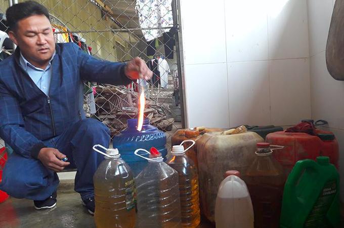 Người dân lọc dầu bỏ vào can, bốc cháy khi bén lửa. Ảnh: H.L