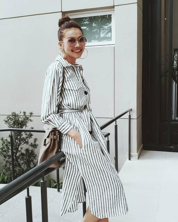 Khi chán các kiểu quần skinny khoe đôi chân dài, Thanh Hằng đổi gió với phong cách nhẹ nhàng cùng thiết kế váy sơ mi kẻ sọc.