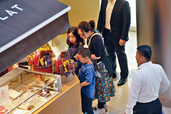Trong khi ba mẹ con lựa chọn chocolate và bánh macaron, vệ sĩ vây xung quanh họ.