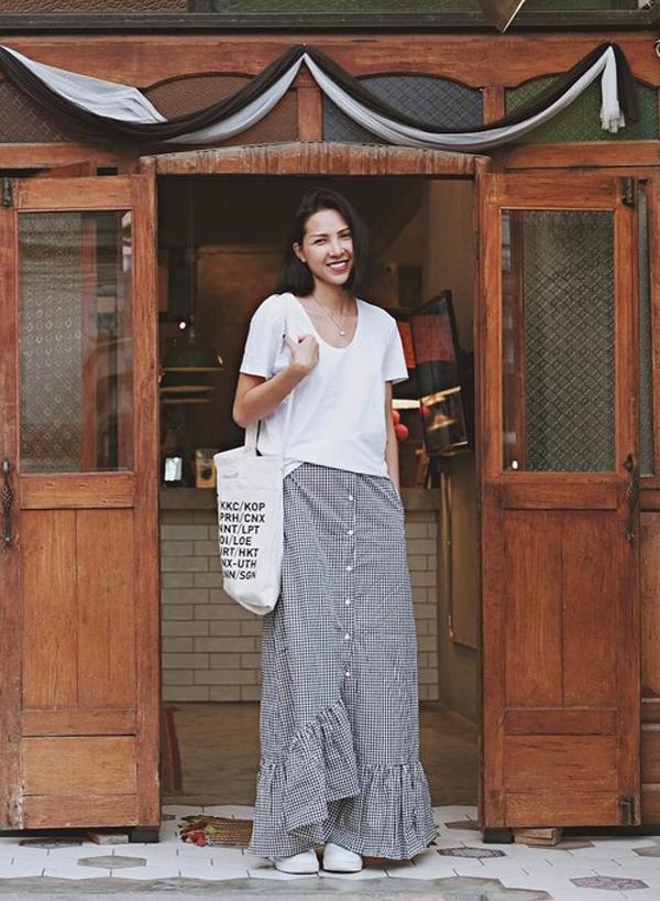 Áo thun trắng được sao Việt lựa chọn bởi dễ sử dụng và thoải mái phối đồ cùng nhiều kiểu dáng quần jean, chân váy midi, maxi, váy ngắn khác nhau. Minh Triệu với hình ảnh phóng khoáng và tự do cùng cách phối áo hợp mốt đi cùng chân váy maxi, túi vải đeo vai.