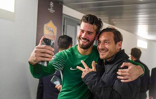 Huyền thoại Totti của Roma cũng vào trong phòng thay đồ chia vui với các đồng đội cũ, chụp ảnh cùng thủ thànhAlisson.