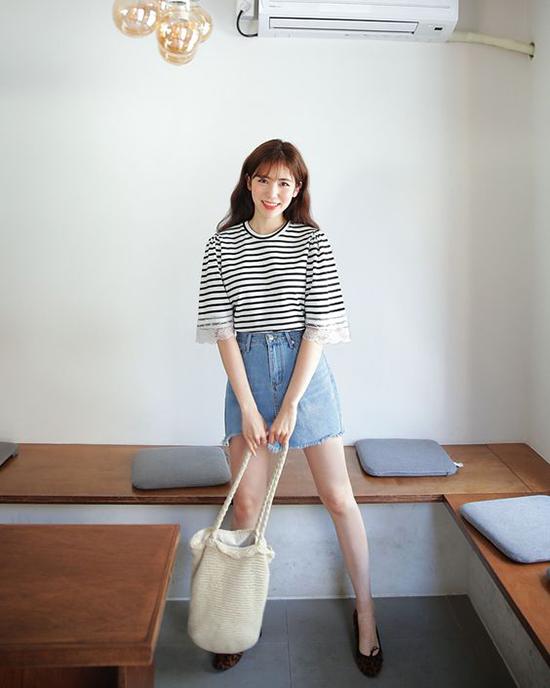 Set đồ đơn giản với cách phối áo thun kẻ sọc, chân váy jean xé gấu và túi đeo vai ton bản phù hợp với những buổi cà phê, mua sắm.