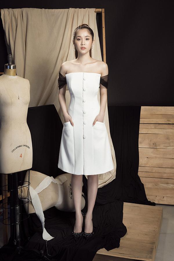 Váy cúp ngực được cắt ráp tinh tế đồng thời được tô điểm bằng những chi tiết nhẹ nhàng như đường trễ vai vải đen, hàng cúc bọc xinh xắn.