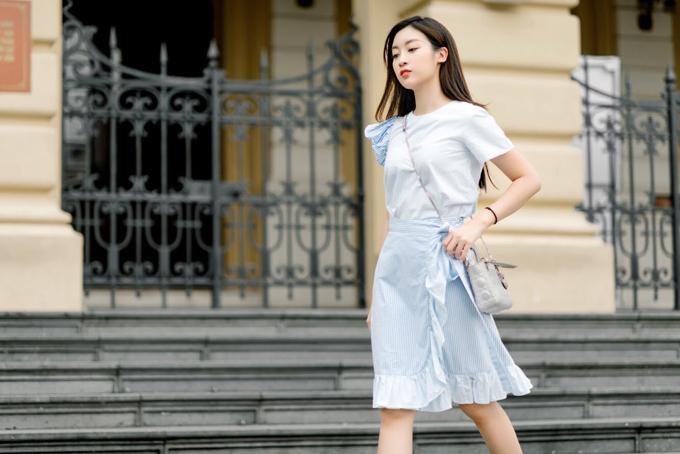 Hoa hậu trông nhẹ nhàng và thanh thoát hơn khi khoác lên người bộ phối áo vải cotton tay áo bất đối xứng và chân váy vạt đắp chéo viền bèo nhún.