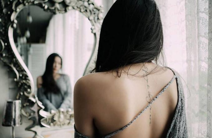 Dọc sống lưng của cô là dòng chữ tiếng Anh: Never forget who you are (Đừng bao giờ quên mình là ai).
