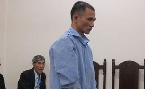 Bị cáo Quang (áo xanh) đứng) tại phiên tòa.