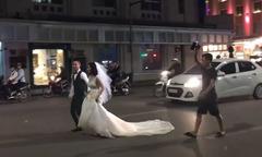 Cô dâu chú rể chạy giữa phố đông người chụp hình