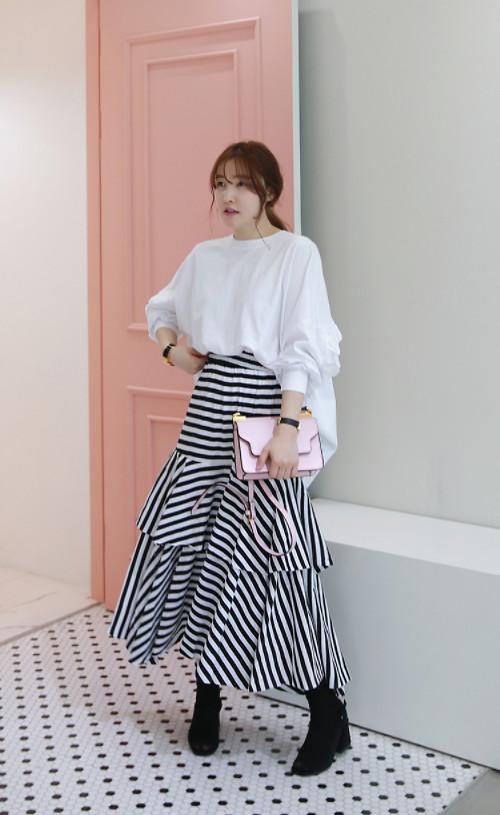Bạn gái văn phòng sẽ có được nét thoải mái và phóng khoáng với áo trắng tay bồng phom dáng rộng đi cùng chân váy xếp tầng kẻ sọc trắng đen.