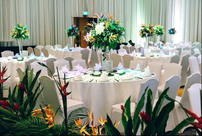 Cô dâu chú rể lựa chọn kiểu bàn tròn, lọ hoa dáng cao để phù hợp với không gian sang trọng của khách sạn 5 sao nơi tổ chức hôn lễ.