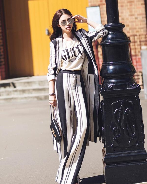 Jolie Nguyễn thể hiện sự phóng khoáng và trẻ trung khi phối áo thun hàng hiệu cùng suit kẻ sọc thiết kế phom dáng rộng.