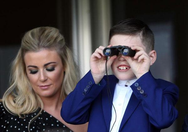 Chàng trai đầu lòng của Rooney thích thú ngắm đua ngựa qua ống nhòm.