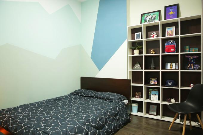 Bức tường vẽ họa tiết đồ họa và chiếc kệ nhiều ngăn là điểm nhấn trong phòng ngủ.