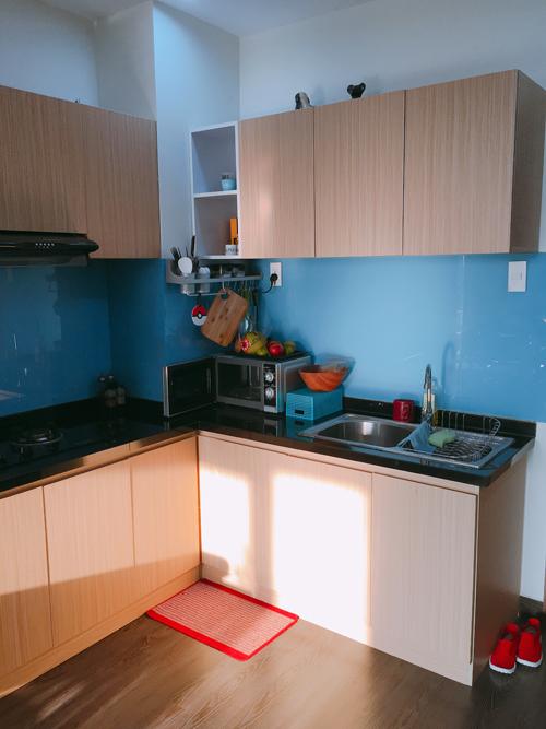 Khu bếp được sắp xếp gọn gàng, tông xanh và nâu sáng. Tuy nhiên, anh dự định sẽ sơn lại màu tủ bếp để phù hợp hơn với tổng thể. Toàn bộ sàn nhà được làm bằng chất liệu vinyl nên không bị tác động nhiều của nắng như sàn gỗ.