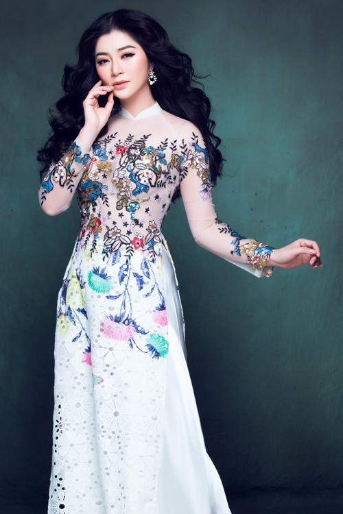Áo dài thêu hoa trên nền chất liệu xuyên thấu phù hợp với không khí của một đám cưới xuân hè, đồng thời tôn lên vẻ đẹp mong manh, thuần khiết cho nàng dâu.