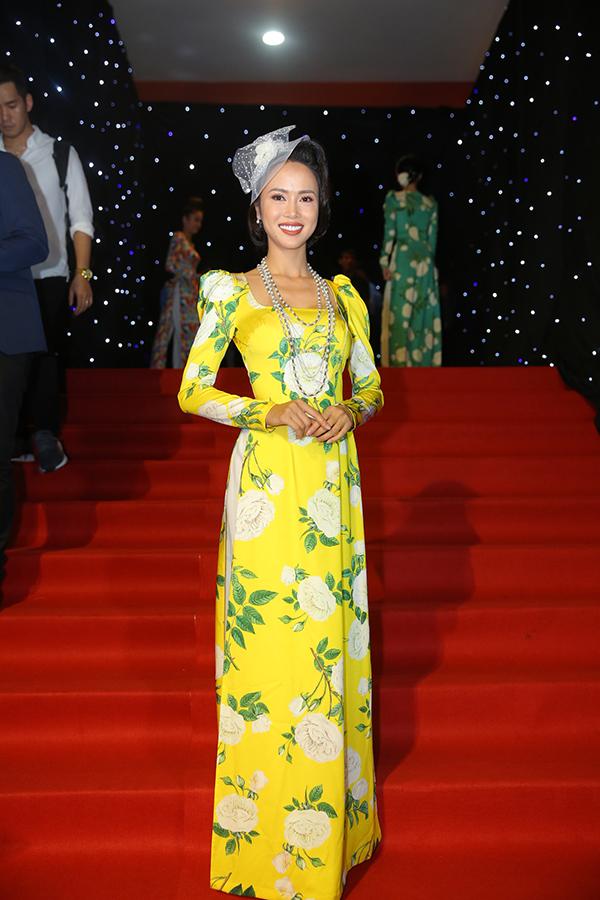 Vũ Ngọc Anh diện áo dài tông vàng rực rỡ đi cùng kiểu dáng đậm phong cách cổ điển của mốt áo tay bồng thập niên cũ.