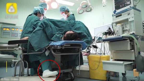 Một bên chân bị bó bột vẫn không cản được nữ bác sĩ tiếp tụccông việc trong phòng mổ. Ảnh: Pear Video.