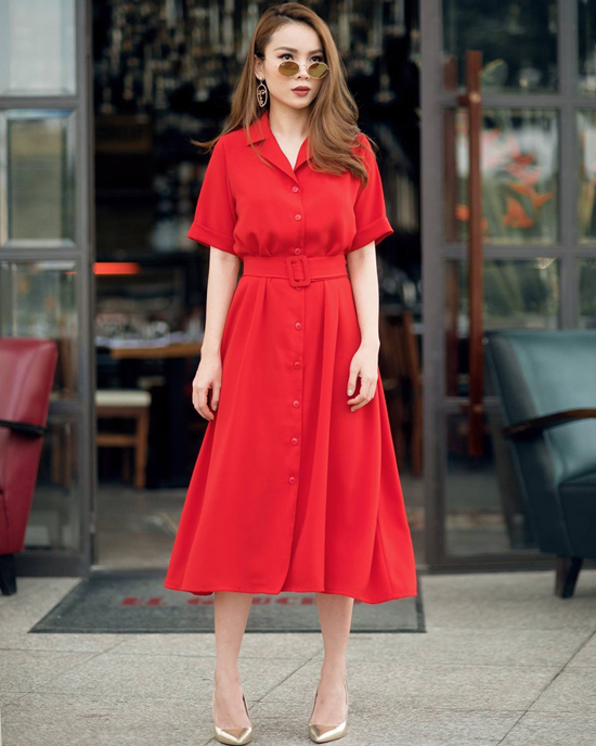 Váy cổ vest với đường nút cài điệu đà đi kèm dây thắt lưng vải tiệp màu được Yến Trang sử dụng để giúp mình trở nên thanh nhã hơn.