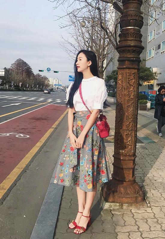 Chân váy midi rực rỡ sắc hoa được Hà Thu kết hợp ăn ý cùng túi đeo chéo hàng hiệu, sandal quai mảnh và áo trắng tây bồng hợp mốt.