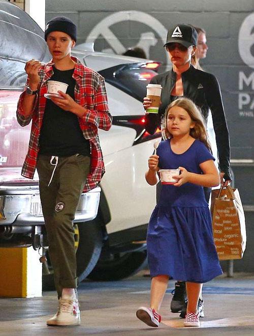 Một ngày trước đó, Vic xuất hiện trên phố cùng hai nhóc Romeo và Harper. Trên tay mỗi bé nhà Becks cầm một hộp sữa chua còn bà mẹ vừa đón sinh nhật 44 tuổi cầm cốc cafe đi sau.