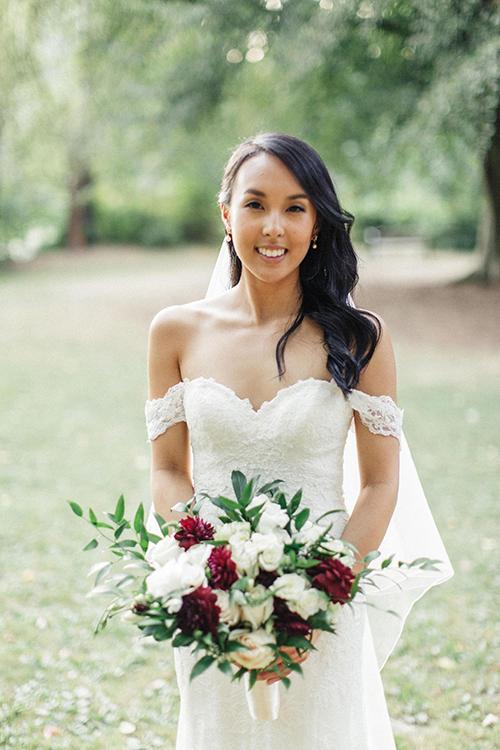 Cô dâu xuất hiện trong bộ váy trắng trễ vai và cầm trên tay một bó hoa cưới đơn giản với sắc đỏ và trắng.