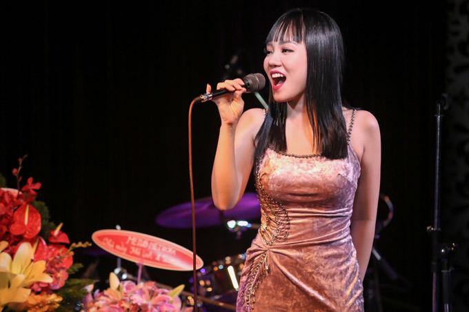 Khả Linh tự tin khoe giọng hát live trong sự kiện tổ chức ở một phòng trà ca nhạc.